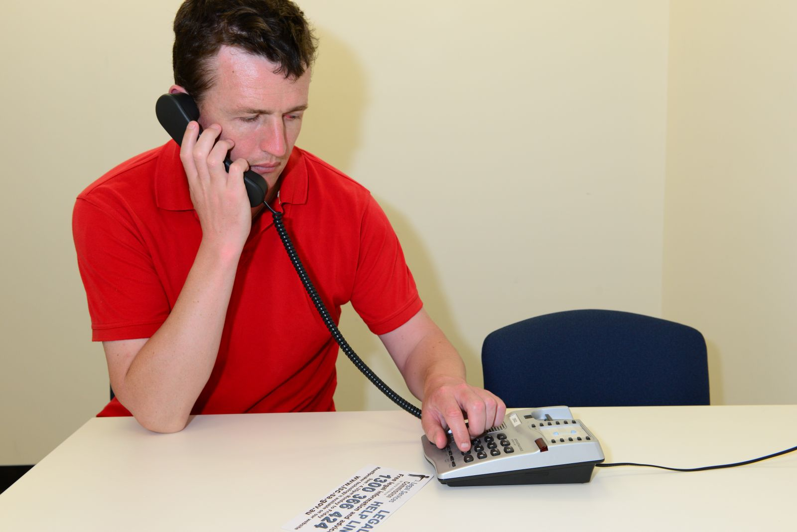 A photograph of a person under arrest making a phone call to get legal advice.