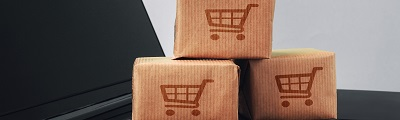 A close up photo of brown paper cartons with shopping cart stamp sitting on lap top